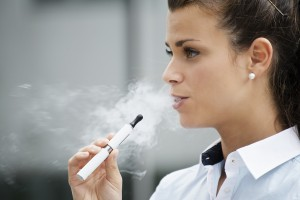 young woman smoking electronic cigarette outdoor office building